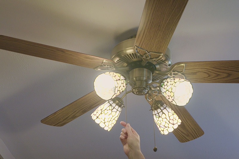 someone turning on their ceiling fan to save energy and money