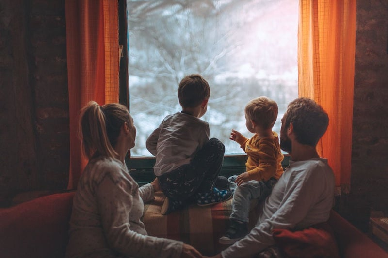 family looking out window in winter.